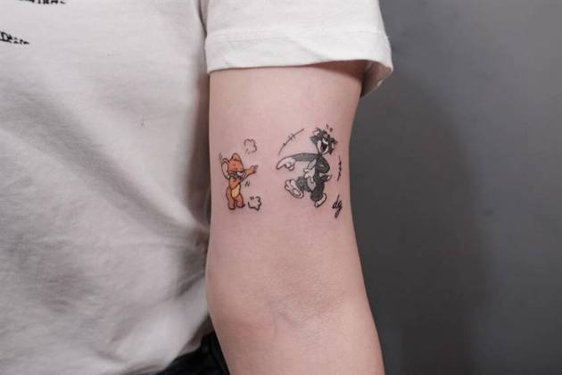 funny small tom and jerry cartoon tattoo design on inner arm