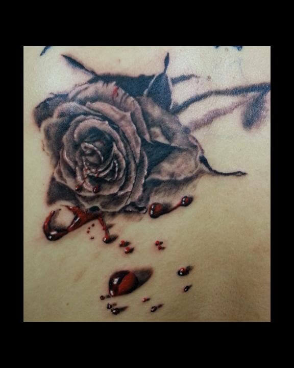 black rose bleeding with drops of red blood tattoo design