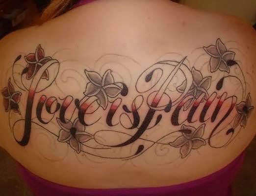 love is pain tattoo in red and black ink font tattoo design with flowers on upper back