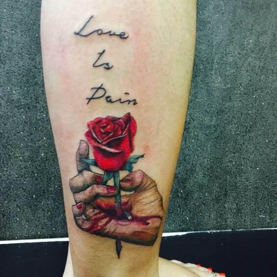 bleeding hand with thorny rose and love is pain quote tattoo design