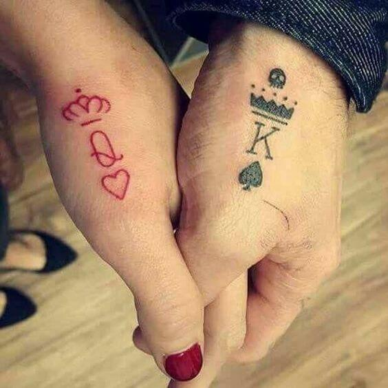 red and black king and queen initials with crowns card tattoos on hands for couples