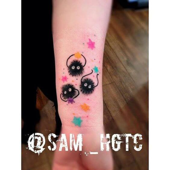 watercolor stars with happy soot sprite tattoos on wrist