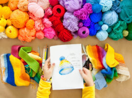 Colorful yarn stacked in a series of colors. Background brown kraft paper. Balls and skeins of colored yarn for knitting. A woman going to knit a hat.