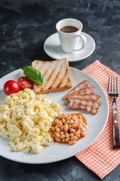 desayuno-huevos-revueltos-tocino-plato-cafe-negro-fondo-alimentos-endecha-plana_290947-1423