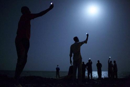 Foto ganadora World Press Photo 2014 de John Stanmeyer -De entre las casi 100.000 fotografías presentadas, estas han sido las mejores empezando por la ganadora absoluta obra de estadounidense John Stanmeyer, retratando a un grupo de inmigrantes africanos buscando cobertura para sus móviles Yibuti