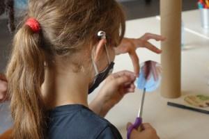 Jeune fille en train de découper du carton pour faire un baton de pluie