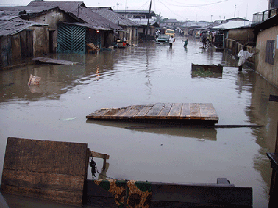Its not the flood water, but rather washed up planks, appear to create a barrier         along this street at Agege, Lagos.  Lagos during rainstorm in pictures Roadblock