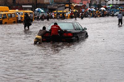 """A motorist needs help to """"swim"""" through a flooded Obafem Awolowo Way, Ikeja,       Lagos."""
