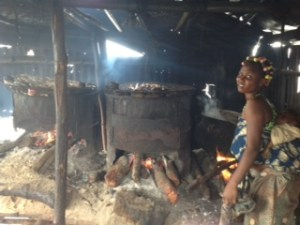 Mother and baby at risk from smoke poisoning as mother processes fresh fish at  SagboKodji Island  Dreams, hope as solar powers century-old Lagos island photo 4 300x225