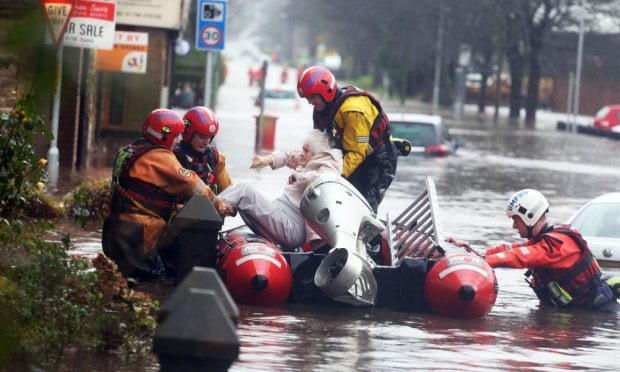 Fire and rescue services evacuate a woman from her flooded home in Littleborough, Greater Manchester. Photo credit: Demotix/Corbis