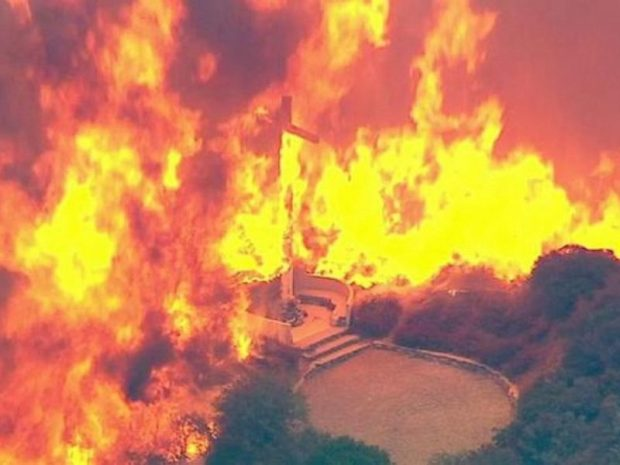 A cross burns in the Blue Cut Fire in the San Bernardino National Forest above Devore on Tuesday, Aug. 16, 2016.