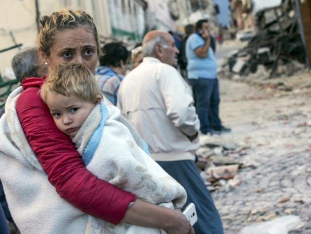 A woman holds a child as they stand in the street following an earthquake, in Amatrice. The magnitude-6 quake was felt across a broad swath of central Italy, including Rome, where residents of the capital felt a long swaying followed by aftershocks. Photo credit: Massimo Percossi/AP  Images: Devastating quake rattles central Italy Italy4 e1472099102248