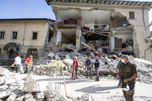 Rescuers stand by a collapsed house in Amatrice. More than 70 people were killed and hundreds injured as crews raced to dig out survivors. Photo credit: Massimo Percossi/ANSA via AP  Images: Devastating quake rattles central Italy Italy5 e1472099268987