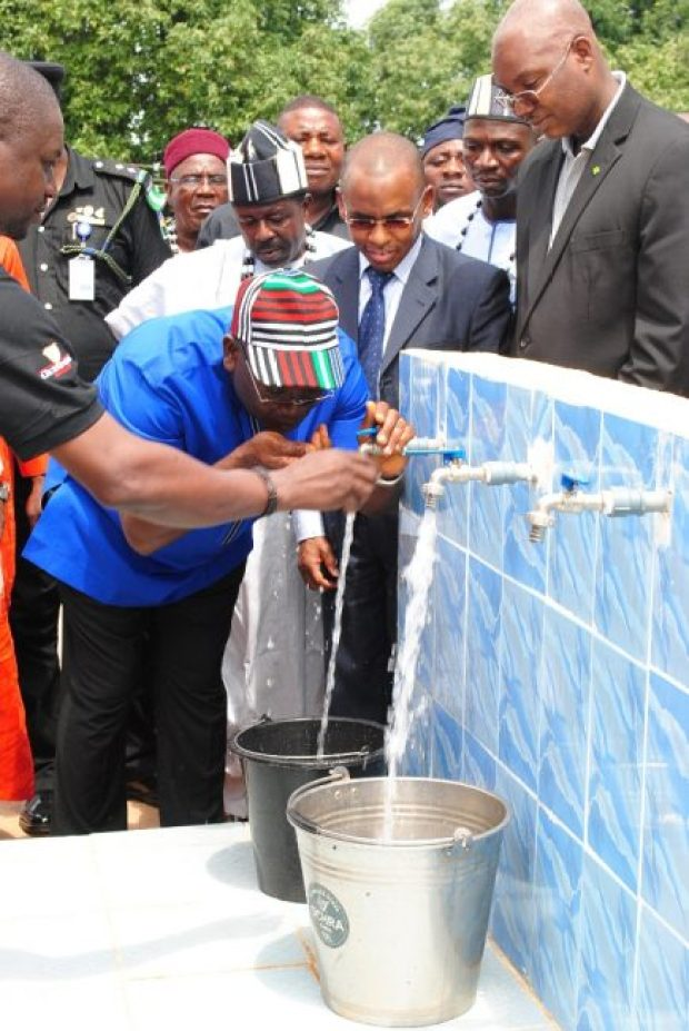 Executive Governor of Benue State, Dr. Samuel Ortom, drinking water as Managing Director, Guinness Nigeria, Peter Ndegwa, looks on during the commissioning ceremony of a water project donated by Guinness Nigeria to the Tyowange community in Benue State