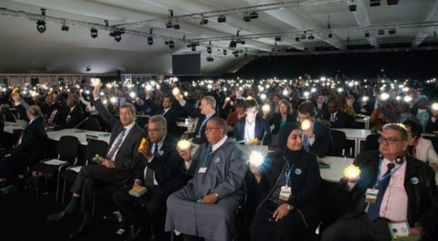 Delegates holding their solar lamps during the opening ceremony. The gesture is a show of solidarity symbolising the transformation to clean technology which is essential to achieve the Paris Agreement goals