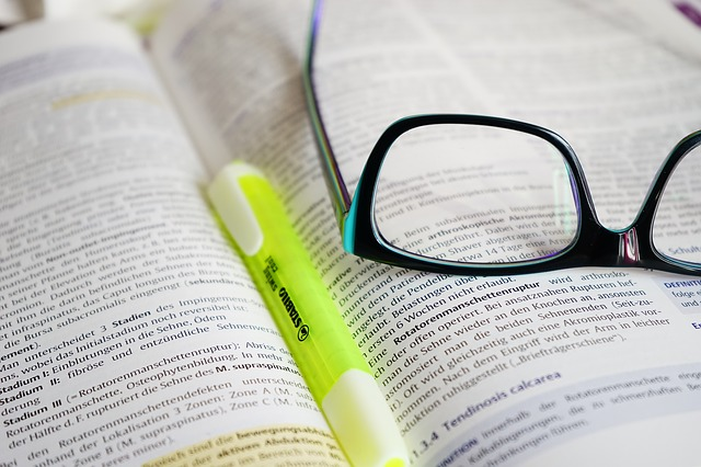 Open book with Highlighter and Glasses on top of it
