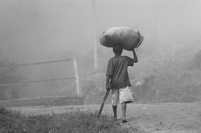 Young boy carrying a bag on his head and walking down the road