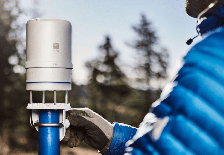 Researcher setting up an ATMOS 41 all-in-one weather station