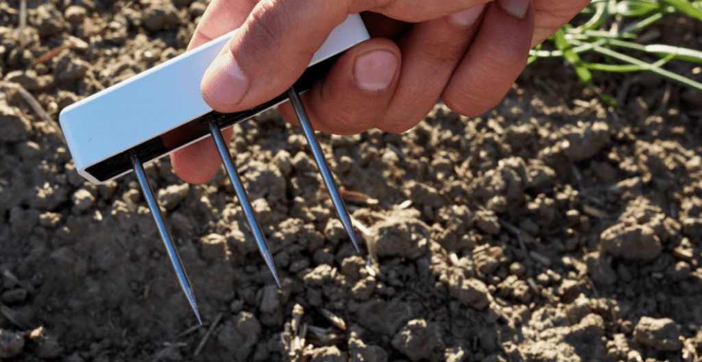 Image of a researcher holding a TEROS-12 soil moisture sensor