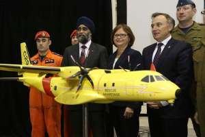 LARS HAGBERG / THE CANADIAN PRESS Defence Minister Harjit Sajjan, third left, Public Procurement Minister Judy Foote and the MP Neil Ellis, second right, for Bay of Quinte pose for pictures at CFB Trenton in Trenton, Ontario, on Thursday Dec. 8, 2016. The federal government says Canada will spend $2.3 billion to replace the military's ancient search-and-rescue planes with 16 new aircraft from European aerospace giant Airbus.