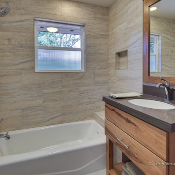 Hall bath with Chroma Tile vanity and porcelain tile tub surround