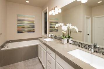 Porcelain tile counters with undermount sinks, glass mosaic backsplash.