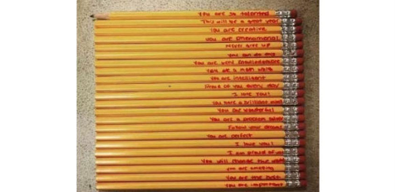 Mãe escreve recados em material escolar para encorajar o filho