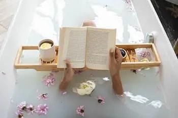 person taking a bath while reading a book