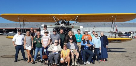 Group shot of the veterans, family and friends in front of vintage yellow airplane