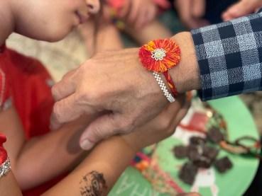 Girl ties rakhi on man's wrist.