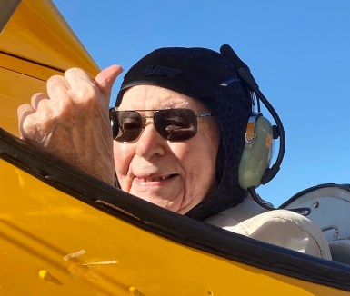 World War II gives the thumbs up sign as he rides in a bright yellow plane