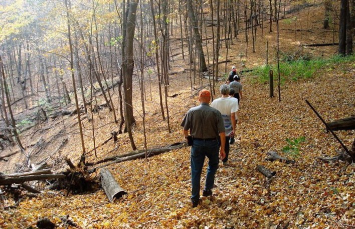 Hikers walk along a trail in the Richard T. Anderson Conservation Area.