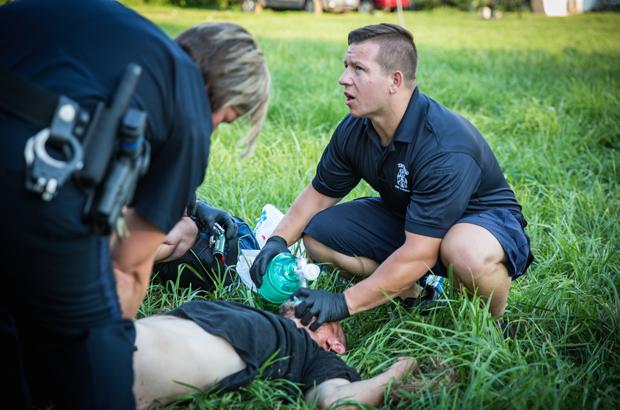 A polícia local e paramédicos ajudam um homem que sofre com uma overdose de drogas no bairro de Drexel em Dayton, Ohio, EUA, em 3 de agosto de 2017 (Benjamin Chasteen/The Epoch Times)