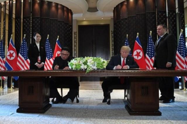 Presidente Donald Trump e o líder norte-coreano Kim Jong-un assinam documentos enquanto o secretário de Estado Mike Pompeo (dir.) e a irmã de Kim, Kim Yo-jong (esq.) observam a cerimônia durante a história cúpula entre Estados Unidos e Coreia do Norte no Hotel Capella, na Ilha Sentosa em Singapura, em 12 de junho de 2018 (Saul Loeb/AFP/Getty Images)