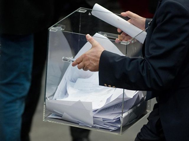 Ein Mitarbeiter des Bundestages trägt nach der Abstimmung über vier Gruppenanträge, die unterschiedliche Regelungen zur Sterbehilfe vorsehen, die Stimmzettel zur Auszählung. Foto: Klaus-Dietmar Gabbert/dpa