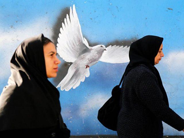 Iranische Frauen vor einer bemalten Hauswand in Teheran. Foto: Abedin Taherkenareh/Archiv/dpa