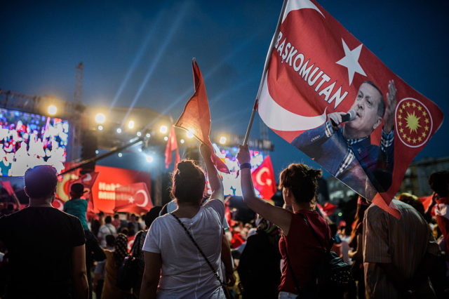 "A Pro-Erdogan supporter holds a portrait flag of Turkish President Recep Tayyip Erdogan reading ""Commander in Chief"" during a rally against the military coup on Taksim square in Istanbul on July 25, 2016. Turkey detained seven fugitive soldiers on July 25 on suspicion of taking part in an attack on the hotel where President Recep Tayyip Erdogan was staying when the failed coup kicked off. / AFP / OZAN KOSE (Photo credit should read OZAN KOSE/AFP/Getty Images)"
