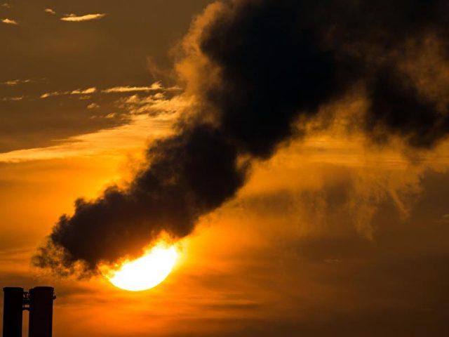 Die Morgensonne scheint hinter qualmenden Schornsteinen eines Blockheizkraftwerkes in Frankfurt (Oder). Foto: Patrick Pleul/Illustration/dpa
