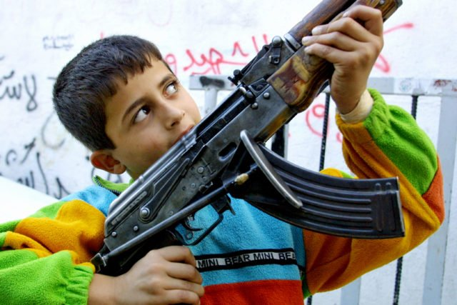 396458 02: A Palestinian boy holds a gunman's AK-47 assault rifle during a round of fighting with Israeli soldiers October 26, 2001 in the al-Azzar refugee camp located within the West Bank town of Bethlehem. Israeli forces maintained their positions in West Bank towns despite calls for their withdrawal from the United States. (Photo by David Silverman/Getty Images)