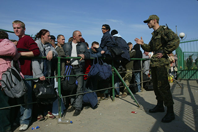 MEDYKA, POLAND - APRIL 16: A Polish border guard talks to Ukrainian people waiting to enter Poland  April 16, 2004 at Medyka, Poland. Thousands of Ukrainians cross daily into Poland attempting to smuggle mainly cigarettes and alcohol to sell in nearby Polish towns. Poland is scheduled to join the European Union on May 1, and Poland's eastern border will become the new eastern border of the European Union. (Photo Sean Gallup/Getty Images)
