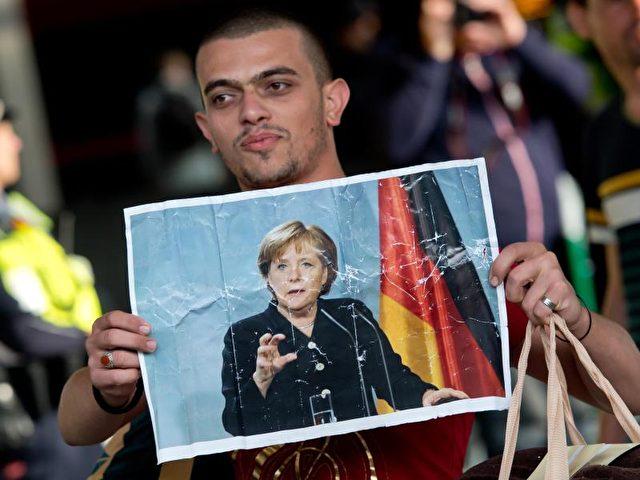 Dank an die Kanzlerin:Ein Flüchtling hält imSpetember 2015 auf dem Hauptbahnhof in München ein Foto von Angela Merkel in den Händen. Foto: Sven Hoppe/Archiv/dpa