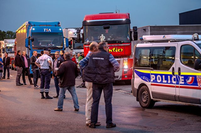 "A police officer speaks with truck drivers gathered near their parked vehicles in Loon Plage on September 5, 2016 ahead of a ""go-slow"" protest on the A16 highway calling for the dismantling of the so-called ""Jungle"" migrant camp in the French northern port city of Calais. French farmers and truckers launched a joint operation on September 5, 2016 to block off main routes in and out of Calais to call for the closure of the sprawling ""Jungle"" migrant camp there. Around 70 trucks began a ""go-slow"" on the main A16 motorway -- the main artery for freight and passengers heading for Britain either via the Channel Tunnel or the Calais port. / AFP / PHILIPPE HUGUEN (Photo credit should read PHILIPPE HUGUEN/AFP/Getty Images)"