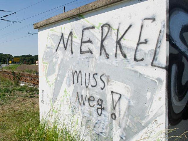 «Merkel muss weg!»-Schriftzug auf einem Bahn-Gebäude bei Bergen auf der Insel Rügen. Die Insel Rügen gehört zum Bundestagswahlkreis von Angela Merkel (CDU). Foto: Stefan Sauer/dpa