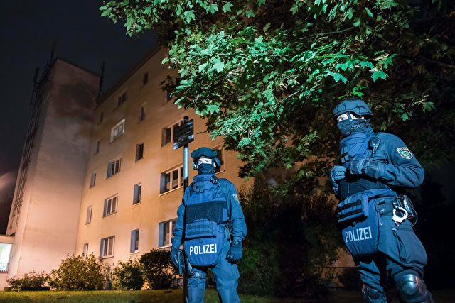"Policemen in protective cllothing stand in front of at a residential building in Chemnitz, eastern Germany, on October 8, 2016. Police found several hundred grams of ""explosive materials"" in the east German apartment of a Syrian man suspected of planning a bomb attack, and arrested three people connected to him. The suspect who remains at large, 22-year-old Syrian Jaber Albakr, could have had ""an Islamist motive"" sources close to the police told AFP.  / AFP / Jens-Ulrich Koch        (Photo credit should read JENS-ULRICH KOCH/AFP/Getty Images)"
