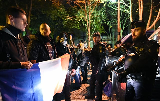 French police officers (L) hold a French flag as they face riot police during a demonstration in Paris on October 20, 2016, to protest over mounting attacks on officers. Hundreds of police have taken to the streets of Paris for a third night of demonstrations calling for reinforcements and stiffer penalties following a string of attacks on officers. Protests also took place in other French cities despite the government's efforts to contain growing anger among police as the issue of safety of law enforcement officers enters the presidential race. / AFP / BERTRAND GUAY (Photo credit should read BERTRAND GUAY/AFP/Getty Images)