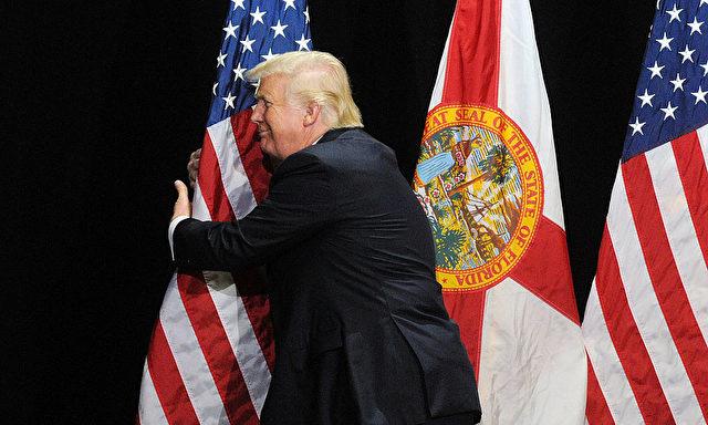Donald Trump umarmt die amerikanische Flagge. Foto: Gerardo Mora/Getty Images