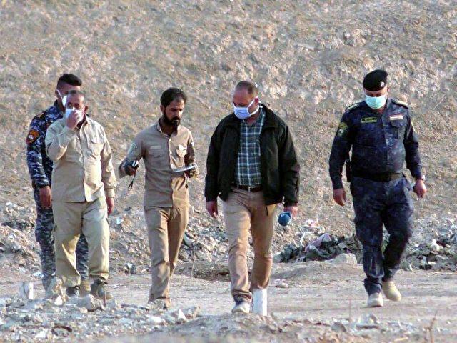 Irakische Offiziere und Forensiker inspizieren den Ort nahe Mossul, an dem beim Vormarsch der Armee gegen die Terrormiliz IS ein Massengrab mit rund 100 Enthaupteten entdeckt worden war. Foto: Stringer/dpa
