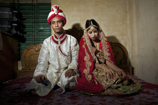 "MANIKGANJ, BANGLADESH - AUGUST 20: 32 year old Mohammad Hasamur Rahman poses for photographs with his new bride, 15 year old Nasoin Akhter, August 20, 2015 in Manikganj, Bangladesh.  In June of this year, Human Rights Watch released a damning report about child marriage in Bangladesh. The country has one of the highest rates of child marriage in the world, with 29% of girls marrying before the age of 15, and 65% of girls marrying before they turn 18. The detrimental effects of early marriage on a girl cannot be overstated. Most young brides drop out of school. Pregnant girls from 15-20 are twice as likely to die in childbirth than those 20 or older, while girls under 15 are at five times the risk. Research cites spousal age difference as a significant risk factor for violence and sexual abuse. Child marriage is attributed to both cultural tradition and poverty. Parents believe that it ""protects"" girls from sexual assault and harassment. Larger  dowries are not required for young girls, and economically, women's earnings are insignificant as compared to men's. (Photo by Allison Joyce/Getty Images)"