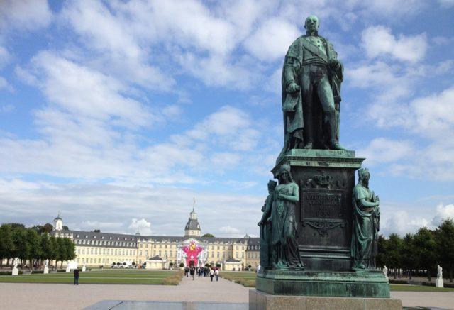 Symbolbild: Karlsruher Schloss mit der Statue des Großherzogs Karl-Friedrich von Baden, der auf die Stadt blickt. Foto: Public Domain
