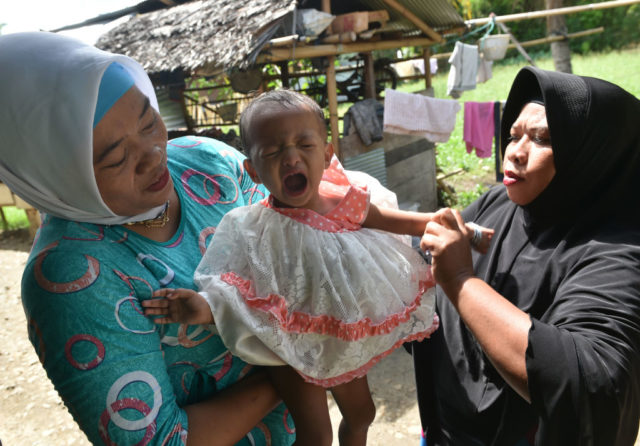 In this photograph taken on February 20, 2017, toddler Salsa Djafar (C) cries after a traditional healer conducted a circumcision in Gorontalo, in Indonesia's Gorontalo province. Female circumcision -- also known as female genital mutilation or FGM -- has been practised for generations across Indonesia, which is the world's biggest Muslim-majority country, and is considered a rite of passage by many.  / AFP PHOTO / BAY ISMOYO / TO GO WITH Indonesia-religion-rights-women,FEATURE by Olivia Rondonuwu        (Photo credit should read BAY ISMOYO/AFP/Getty Images)